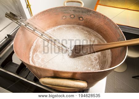 Factory of the production of delicious caramel candies. First step. Boiling syrup of sugar in copper pot with thermometer and big spoon. White colour for the syrup