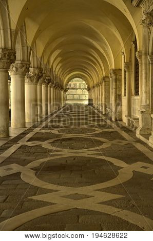A passageway in Venice with repetitive arches.