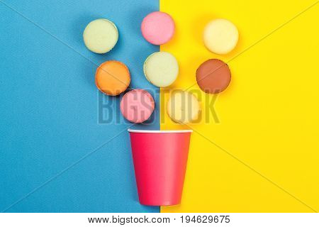 Colorful Macaroons Falling Into Red Paper Cup. Minimal Concept. Appetizing Macaroons On Blue And Yel