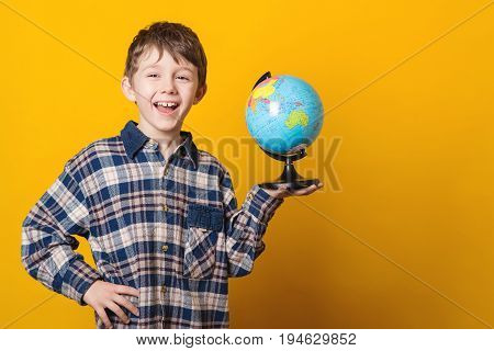 Portrait Of Little Cute Boy With Globe. Isolated Over Yellow Background.