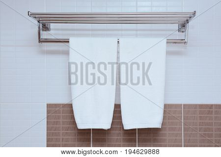 White Towel Hanging On Bathroom Wall With Hanging Towel