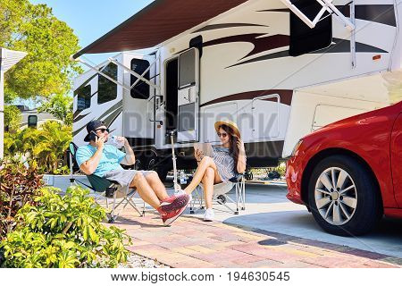 Couple With Electronic Devices Sits On Chairs Near Camping Trailer