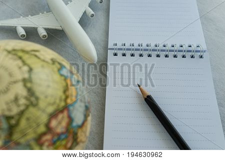 World travel concept with pencil on white note paper toy airplane and small globe on white background.