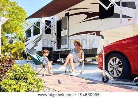 Mother and son sitting near camping trailer smiling. Woman and kid relaxing on chairs near car and palms. Family spending time together on vacation near sea or ocean in modern rv park