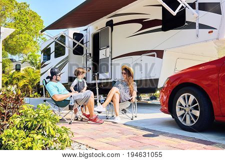 Young Family Sits On Chairs Near Camping Trailer And Car