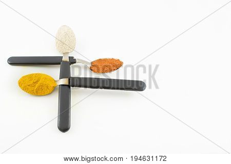 Three spoons crossed with condiments on a white background.