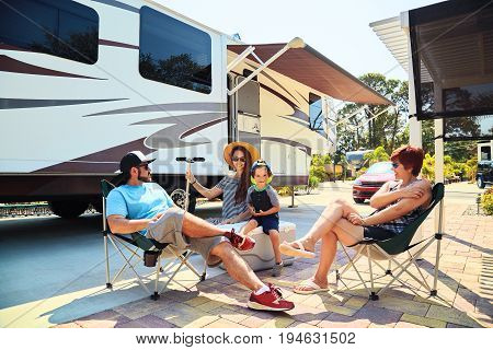 Motherfatherson and grandmother sitting near camping trailersmiling.Womanmenkid relaxing on chairs near car.Family spending time together on vacation near sea or ocean in modern rv park