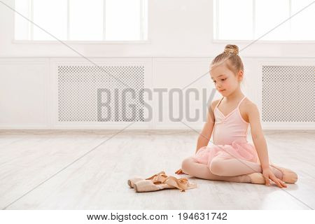 Little girl looking at pointe shoes, copy space. Cute baby dreaming to become ballerina. Classical dance school background, practicing for children