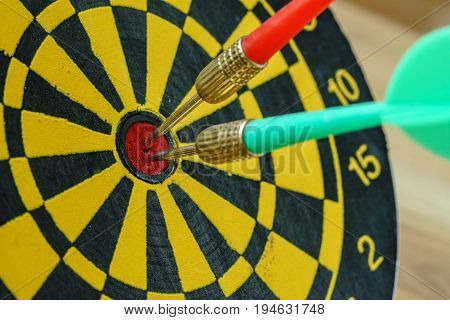 Green and red darts pin in the center of dartboard as business goals or targets concept.