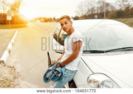 Handsome Man In A White T-shirt Near A White Car. Travel By Car