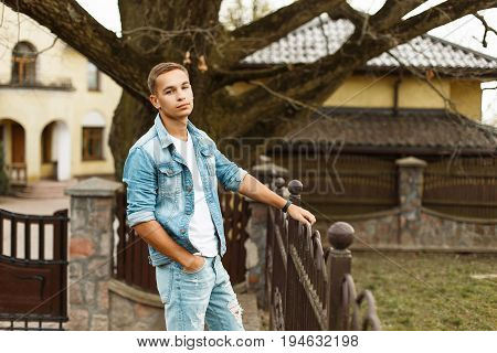 Handsome Fashionable Man In A Denim Jacket With A White T-shirt And Torn Jeans Near The Fence