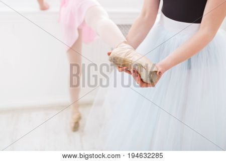 Young ballet teacher and students ballerina in choreography class of ballet school, pointe closeup