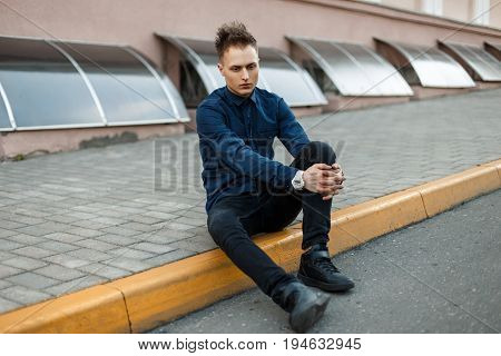 Young Guy In Black Sneakers And Jeans With A Blue Shirt Sitting On The Curb