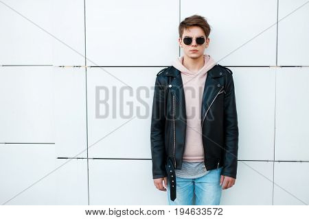 Young Man In A Black Leather Jacket And A Pink Sweatshirt Near A White Wall. Vintage Sunglasses Avia