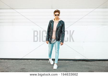 Stylish Handsome Young Man With Sunglasses In A Black Leather Jacket, Blue Fashionable Jeans And Whi