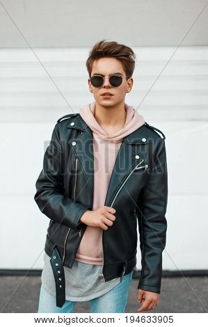 Young Handsome Man In A Black Branded Leather Jacket And A Pink Sweatshirt Near A White Metal Wall