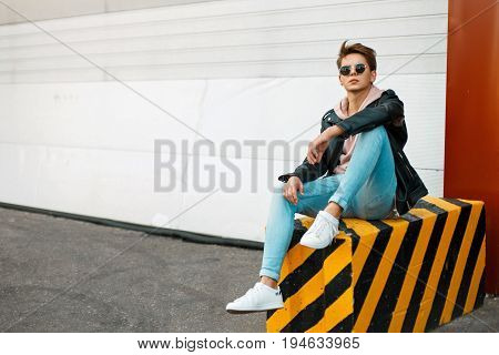 Stylish Handsome Young Man In A Black Leather Jacket, A Pink Sweatshirt And White Sneakers Sits On A