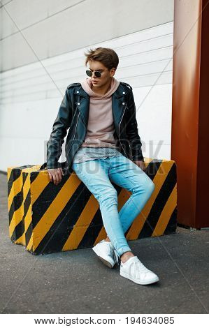 Handsome Young Man With Sunglasses In A Black Leather Jacket, Blue Jeans And White Sneakers Sits On