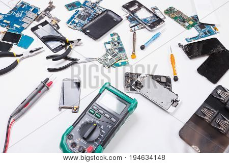 Multimeter and broken electronics at repair shop. Technician workplace with instruments and disassembled smartphones components, top view.