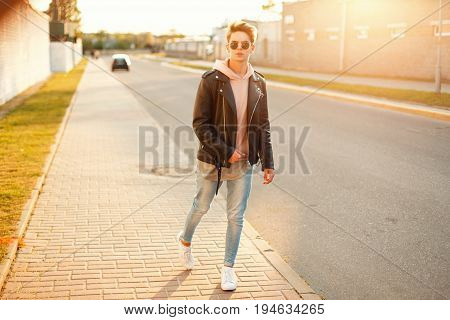 Handsome Man In A Black Leather Jacket And White Sneakers Walking On The Street At Sunset