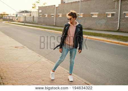 Handsome Young Man With Sunglasses In A Black Leather Jacket, Blue Jeans And White Shoes On The Stre