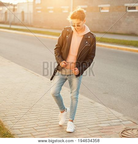 Handsome Young Male Model With Sunglasses In A Black Leather Jacket, Pink Sweatshirt, Blue Jeans And