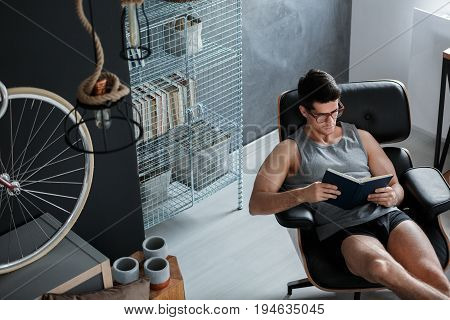 Young handsome man reading a book sitting in armchair
