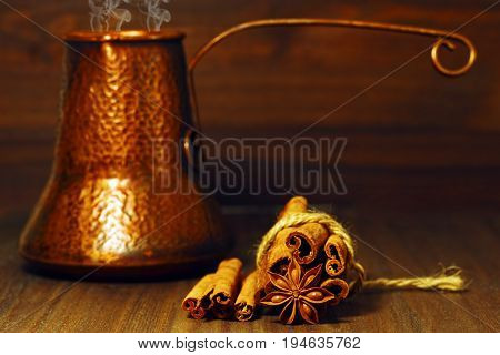 Copper coffee pot in turkish style with fresh coffee with cinnamon and anise