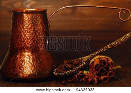 Traditional eastern style copper coffee pot with roasted coffee beans and spices on the table