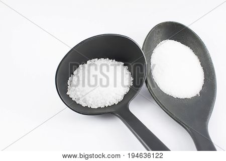 Spoon with fine salt and ladle with thick salt.