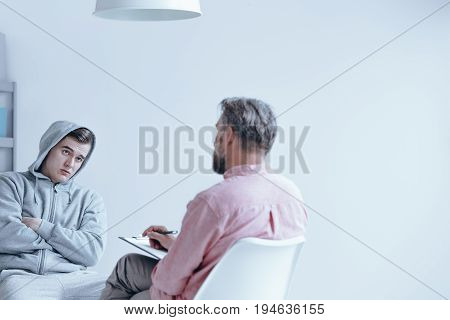 Troubled teenager having an individual session with a therapist