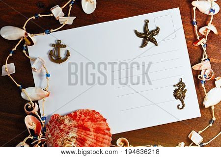 Message from travel concept with sea shells copper pendants and postcard poster
