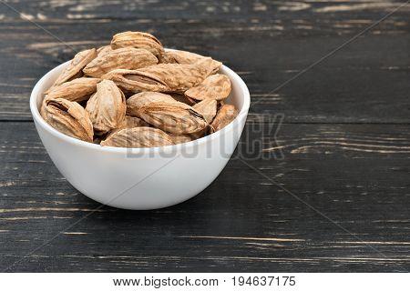 Uzbek almonds in a white bowl on a dark table