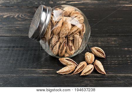 Wild uzbek almonds in a jar on wooden background