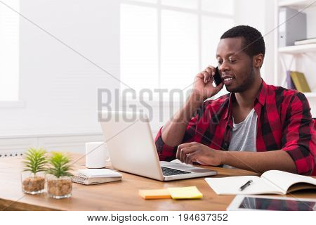 Satisfying call. Young black businessman in casual has mobile phone talk in modern white office interior.