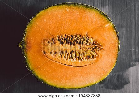 Melon texture on wooden background. Melon background. Close up view of melon cut in a half on wood background. Fresh fruit. Macro view of cut melon surface.