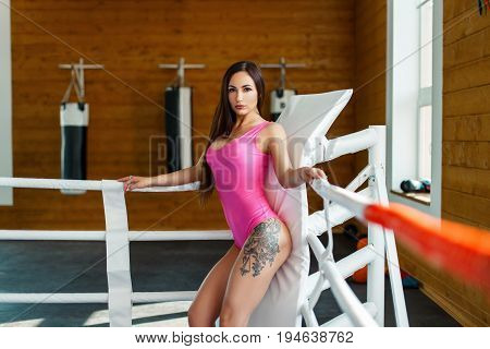 Sexy Young Woman With Tattoo In Pink Body Sportswear Posing In The Ring