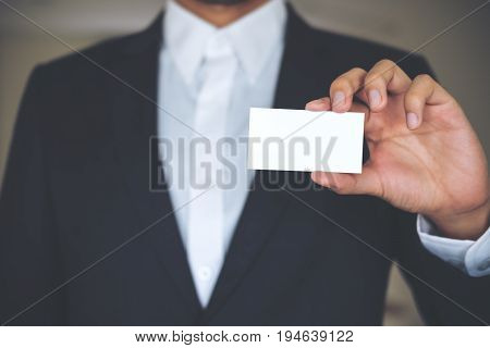A business man in white shirt and gray suit holding and showing empty business card