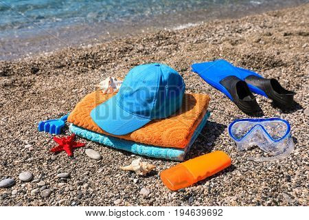 Beach towels, cap, children's toys, seashells, mask, fins and sunscreen on the beach on the sea background, summer family vacation by the sea concept. Horizontal. Close-up.