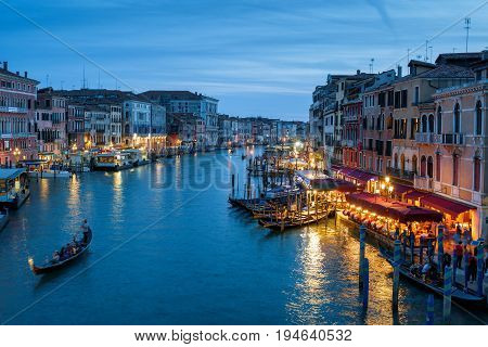 Grand Canal with gondolas at night in Venice, Italy. Grand Canal is one of the major water-traffic corridors and tourist attraction in Venice.