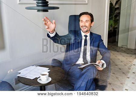 Hello. Happy man is waving arm to passerby through window while sitting in cozy cafeteria. He is holding business journal and laughing