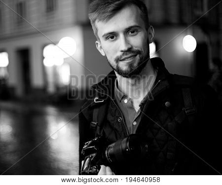 Young male photographer stands on city street in evening. In background there are night city lights. Black and white image. Self-portrait.
