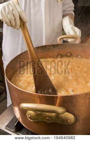Factory of the production of delicious caramel candies. First step. Boiling syrup of sugar in copper pot with thermometer and big spoon. Brown colour for the syrup. Hands of the employee