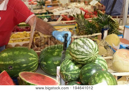 Greengrocer sells watermelons in a banquet of the local market