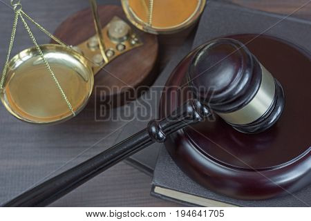 Wood gavel soundblock scales and stack of old books bound in leather on the wooden background