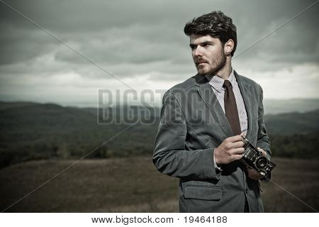 Vintage Photographer holding  a folding camera in his hands