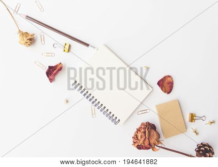 notebook paper pencil dry roses sticky note pine and paper clip on white background