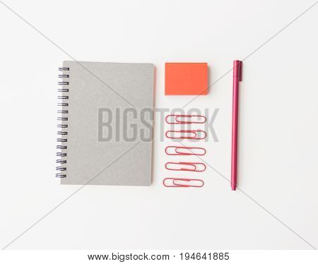 notebook paper red sticky note paper clip and pen on white background flat lay