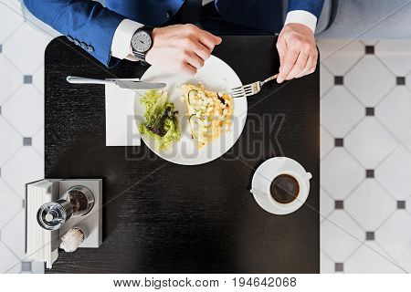 Close up of male hand with wristwatch. Man is checking time while having lunch in cafe. Top view