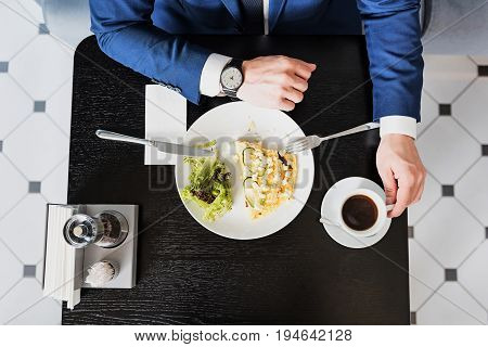 Time is money. Top view of busy businessman looking at watch on his hand. He is eating dish and drinking coffee in restaurant. Close up